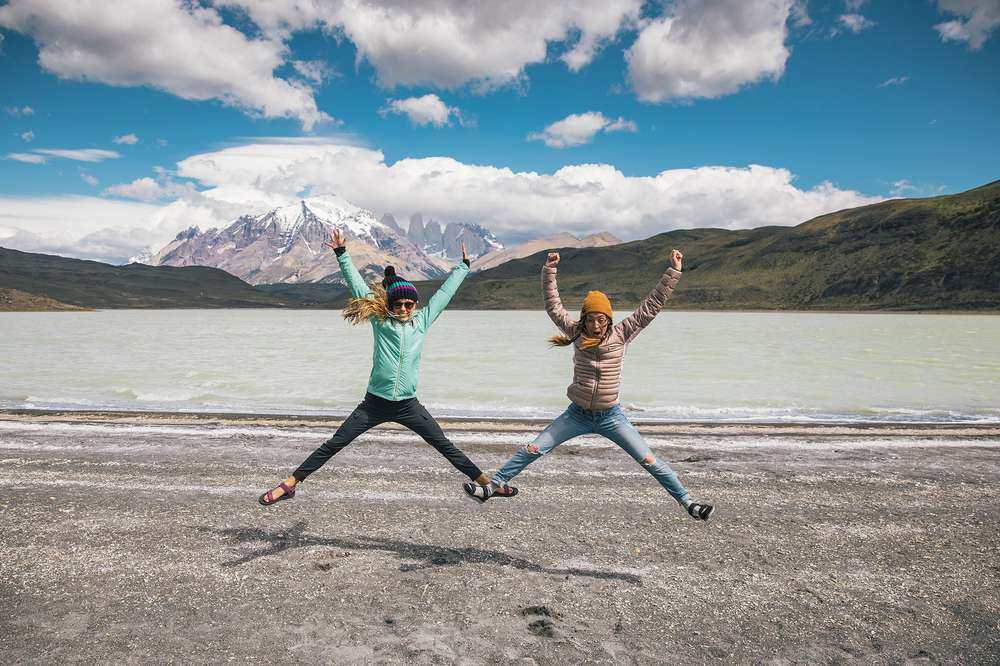 Women jump by a lake in Patagonia