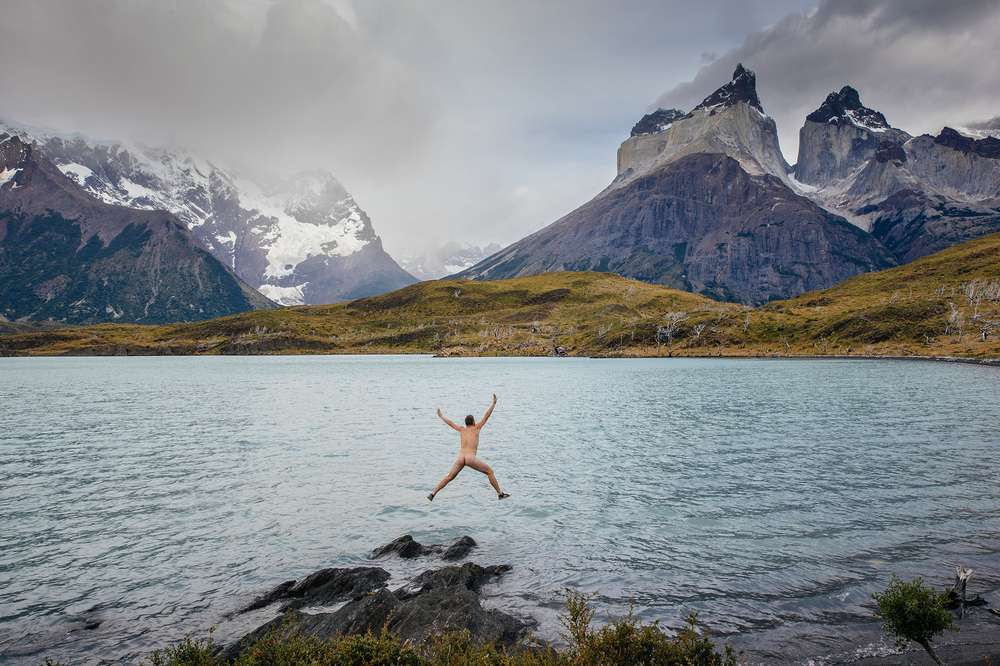 Nude man jumping into lake Patagonia