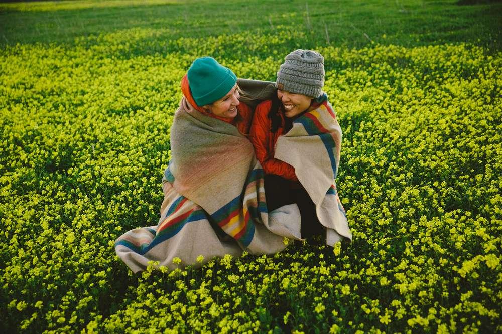 Two women laugh in blanket Santa Cruz