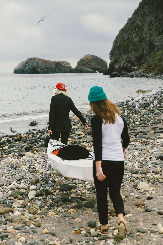 Two women carry Oru Kayak to ocean Santa Cruz