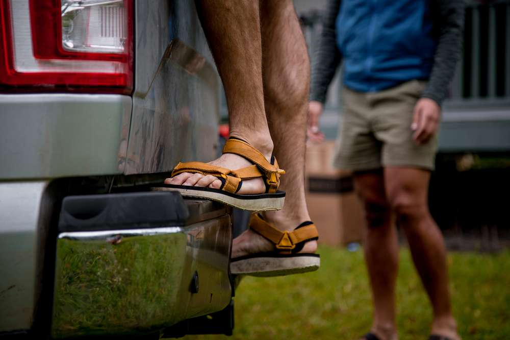 A man's feet on the back of a truck, wearing the Original Universal Premier sandal in Mustard.