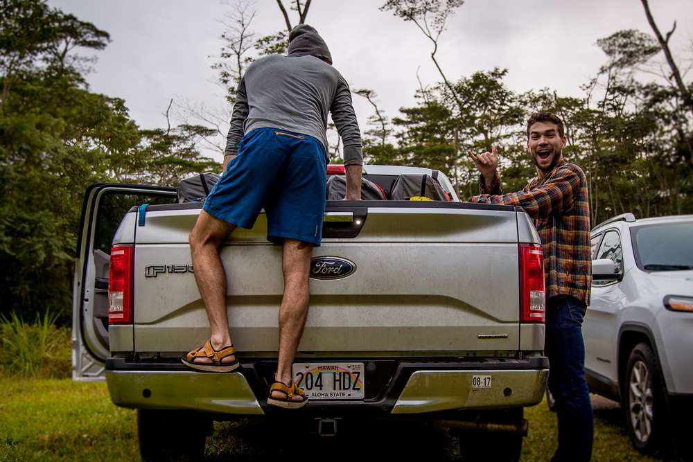 Andy Cochrane climbing in the back of a truck packed with foldable kayaks.