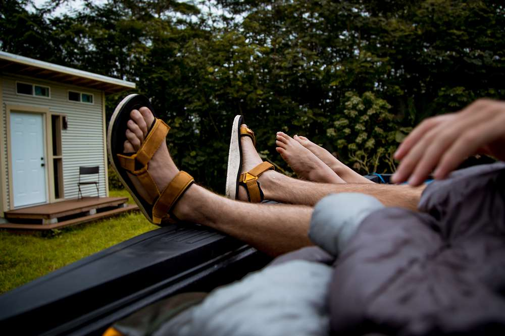 A man's feet hang out the back of a truck wearing Teva sandals.