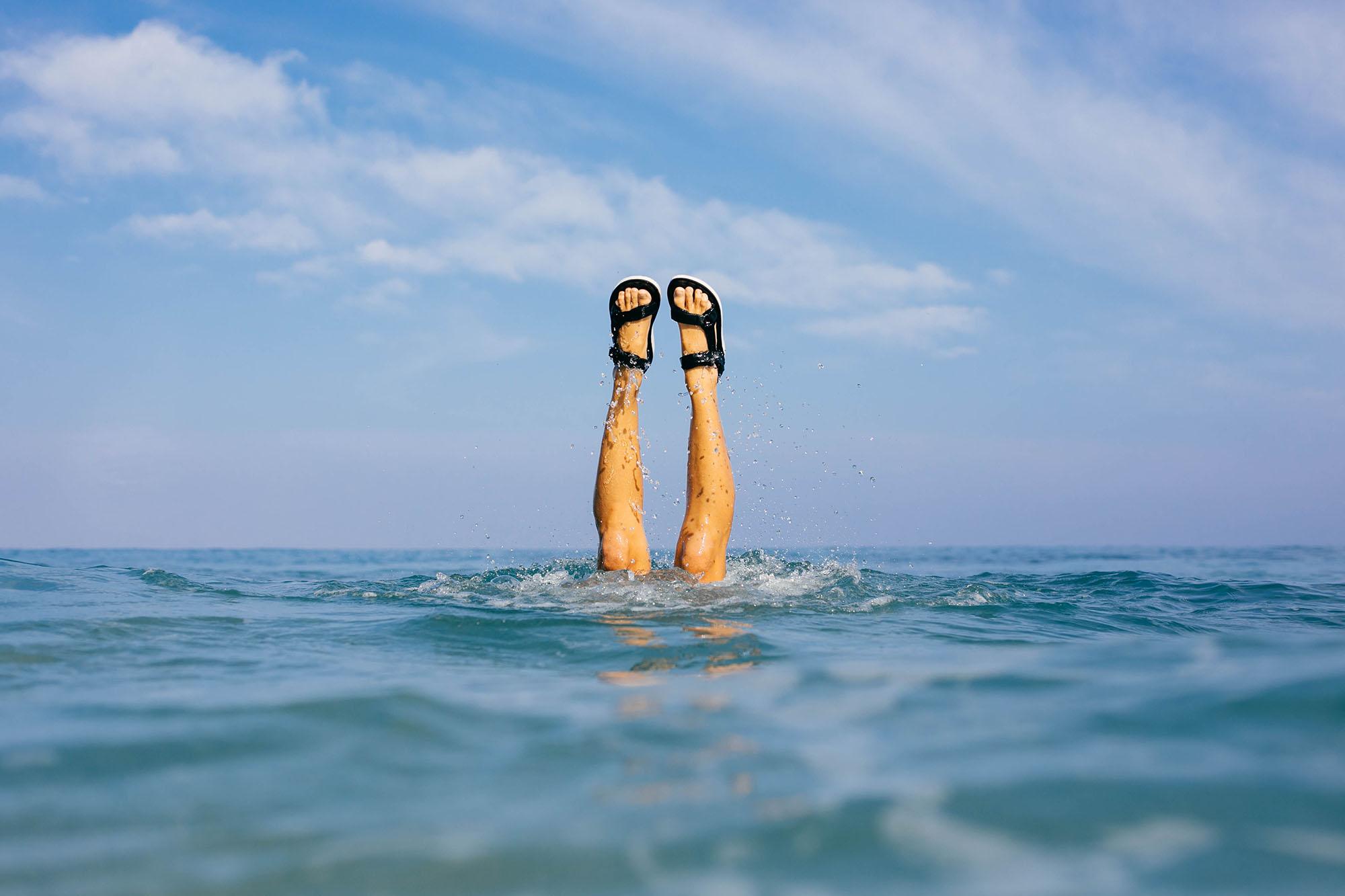 Tara Michie does a handstand in the ocean wearing her Teva Original Universal Premier sandals.