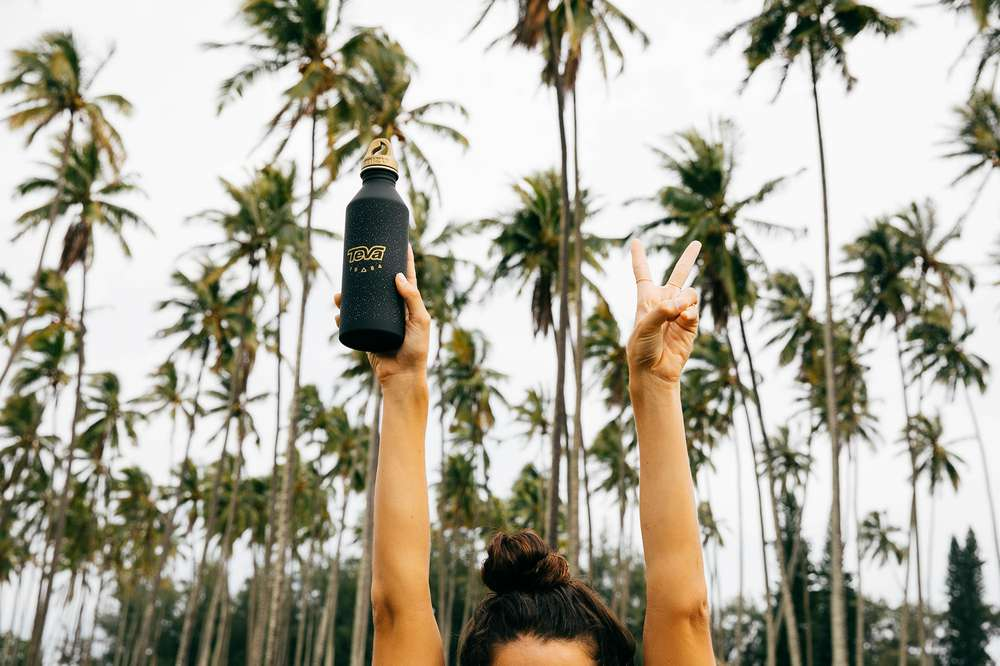 A girl holds her Teva water bottle in the air in front of palm trees in Hawaii.