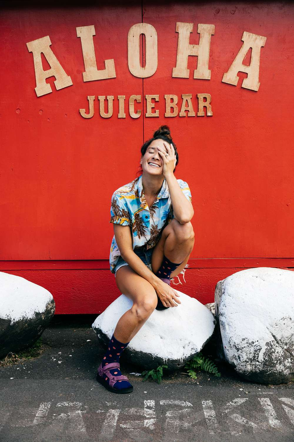Tara Michie sitting on white painted rocks outside a juice bar in Hawaii.