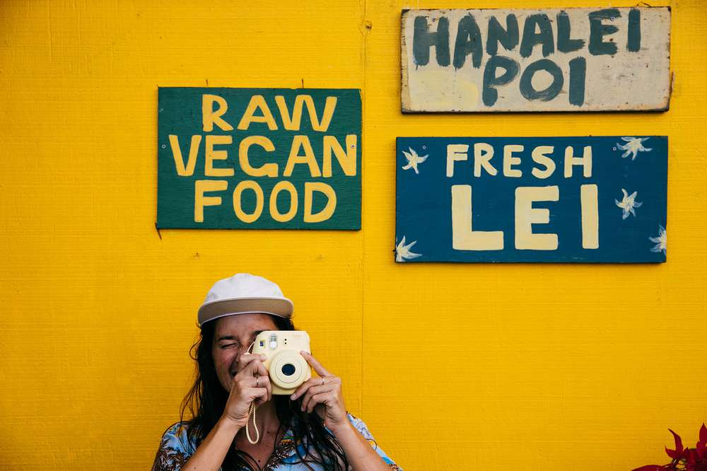 Tara Michie takes a photo with her Fuji Instaxx camera by a yellow wall.