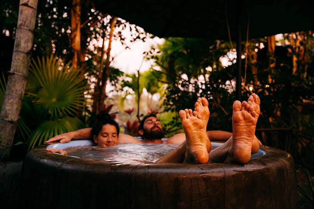 A couple relaxes in a wooden hot tub in Hawaii.