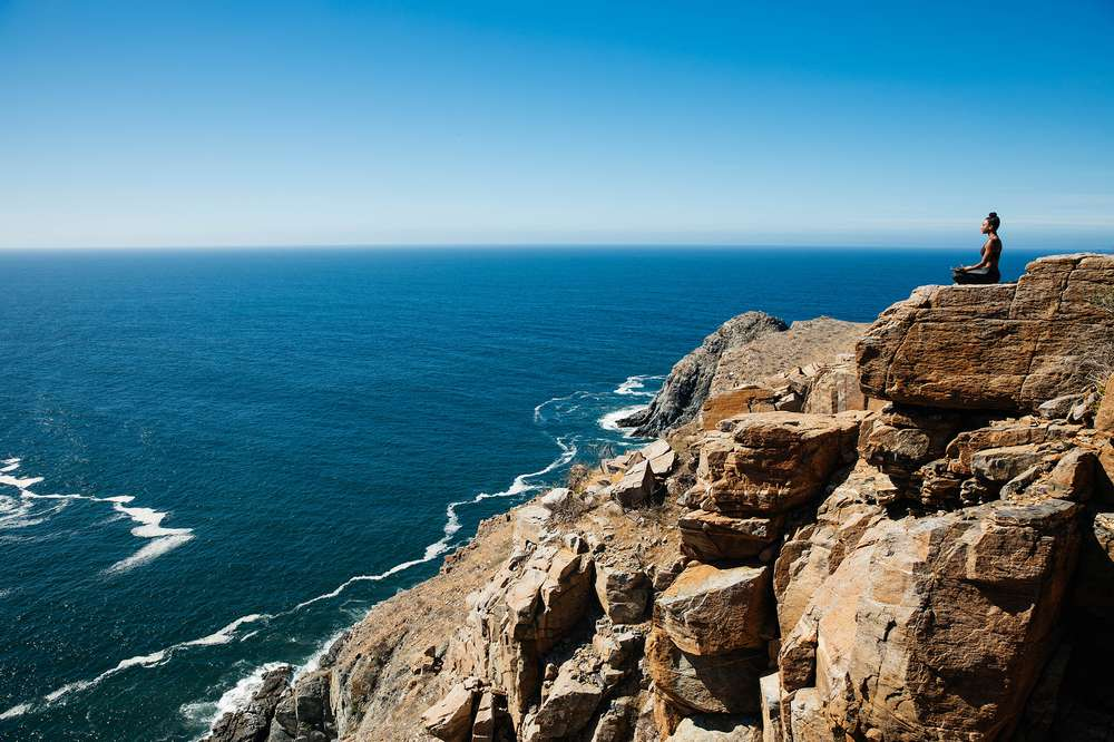 A woman sits cross -legged on a bluff overlooking the ocean in Todos Santos, Mexico.