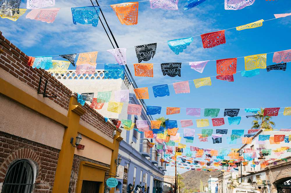 Colorful banners hang above a street in Todos Santos, Mexico.