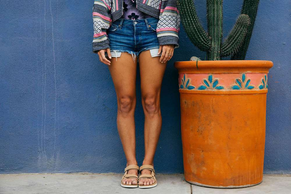 Tara Michie stands next to a potted cactus while wearing the Teva Original Universal Premier Leather sandal in tan.