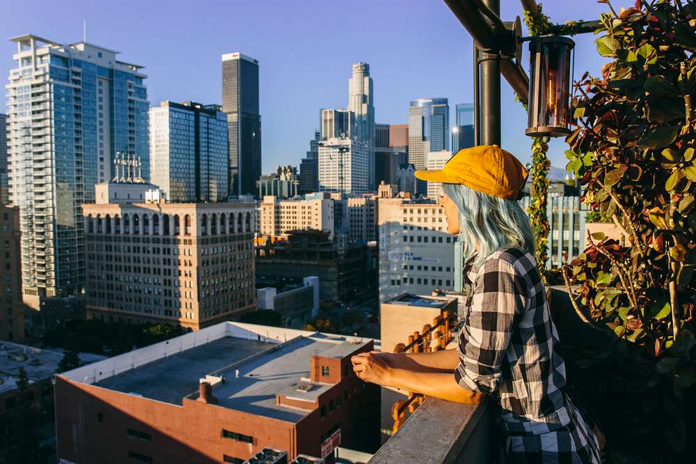 Kate Rentz looks over downtown LA from balcony.