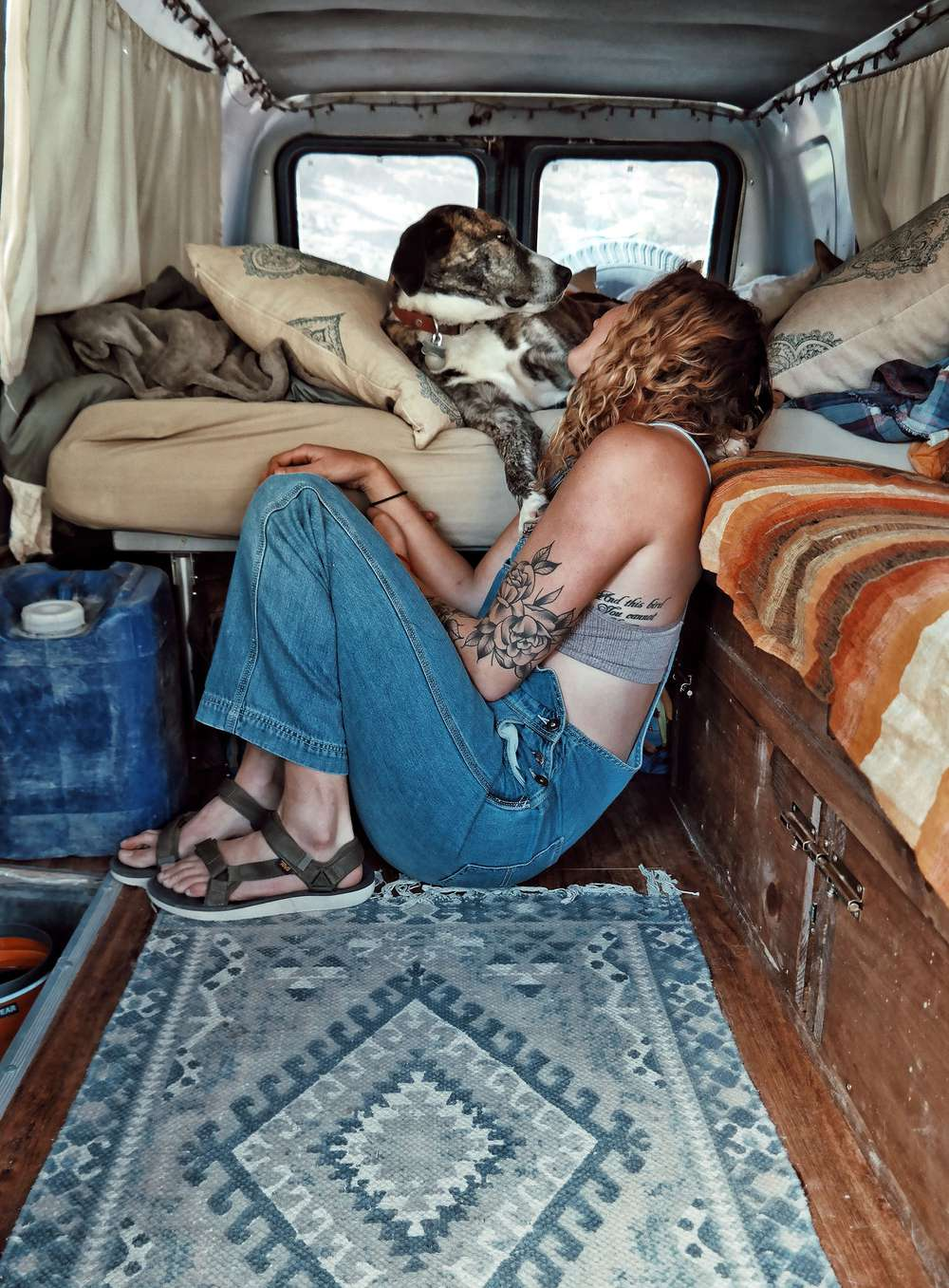 Brianna Madia looking at dog while sitting on floor of van wearing overalls