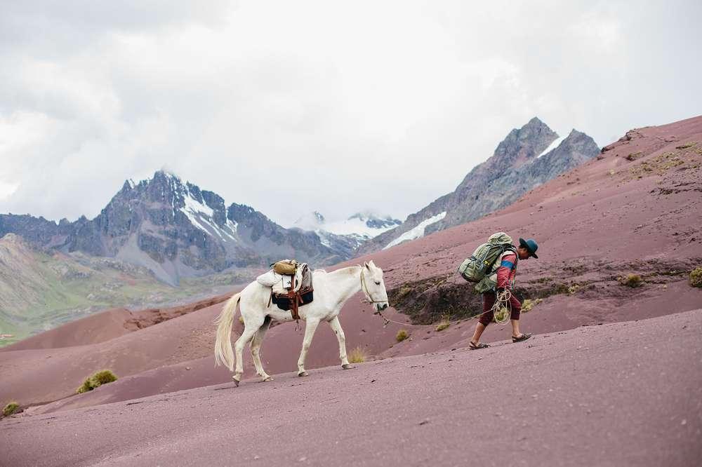 Man walking horse in Andes Peru
