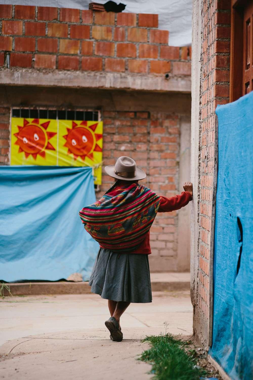 Woman wearing shawl street corner in Peru