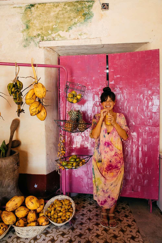 Tara Michie stands by fruit in Cuban shop