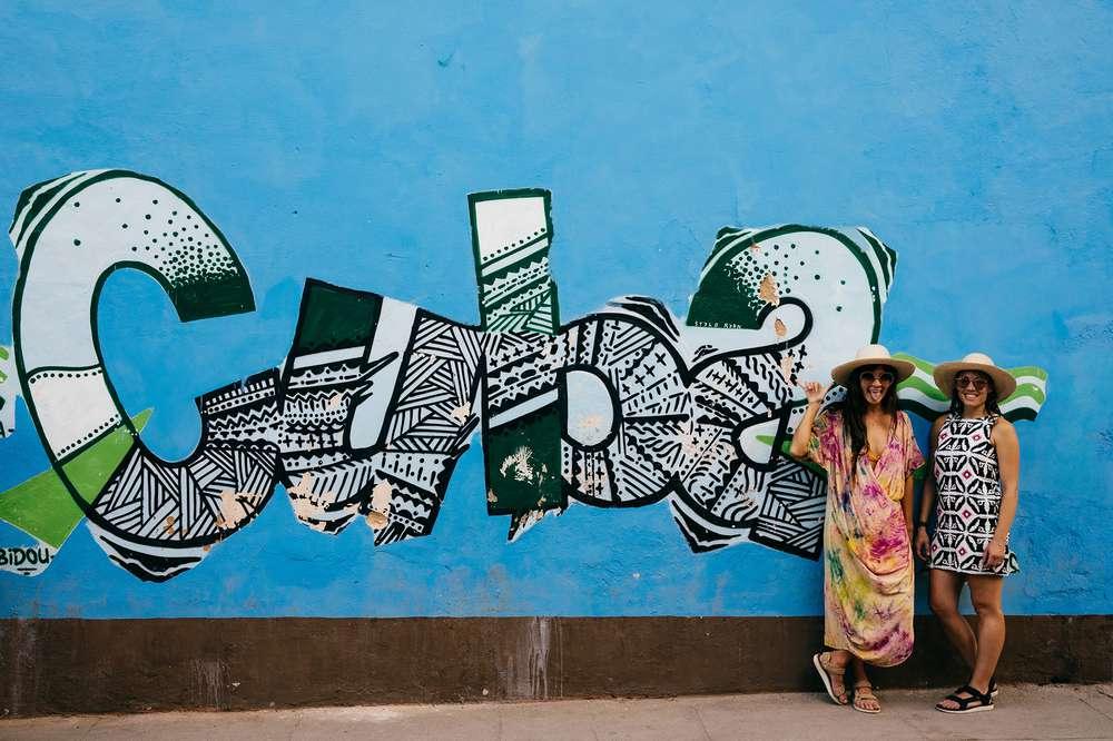 Women pose next to graffiti in Cuba