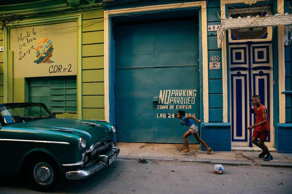 A child runs by a garage in Cuba