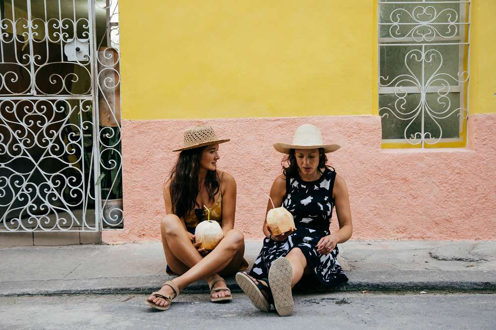 Women drink from coconuts on curb in Cuba