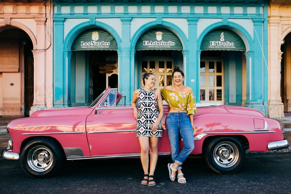Women leaning on vintage car Cuba