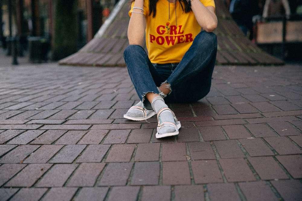 Girl wearing socks and Teva sandals sitting on brick road