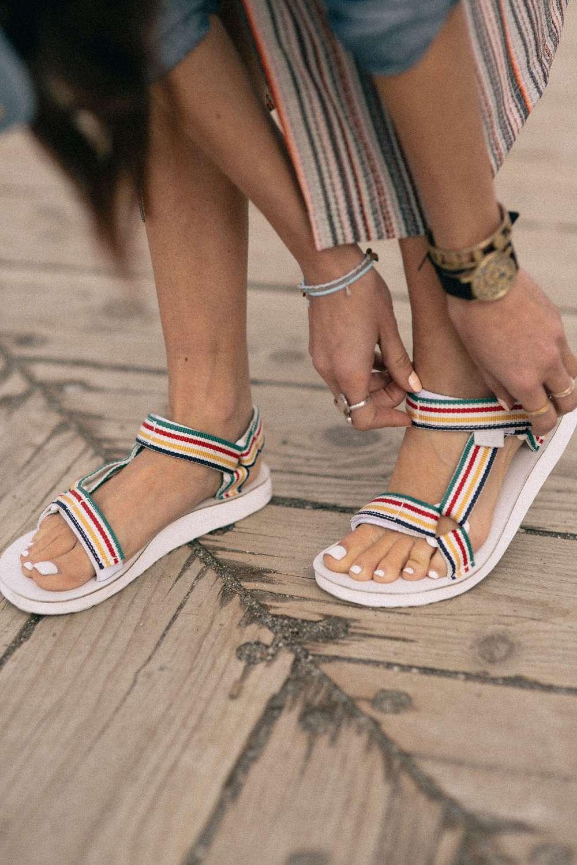 Woman adjusting Teva X Hudson's Bay collab sandals.
