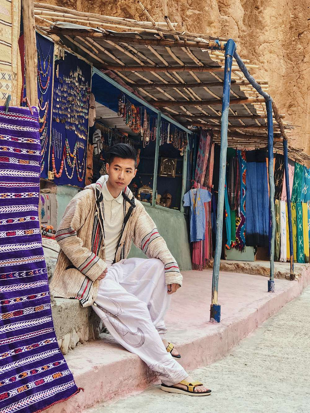 Tommy Lei sitting in marketplace in Morocco
