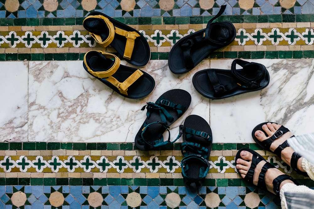 Four Teva sandals on tiled floor