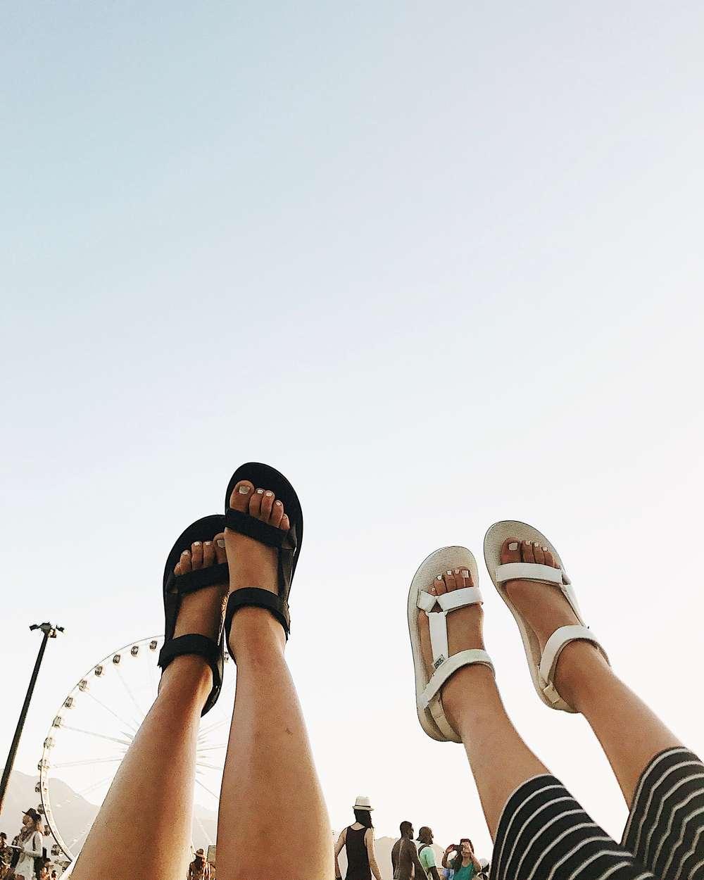 Feet in air wearing Teva sandals