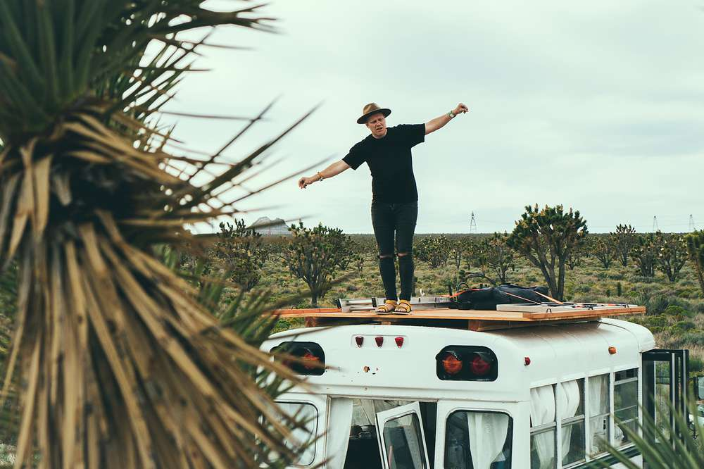 Man standing on Sasquatch the Bus in desert