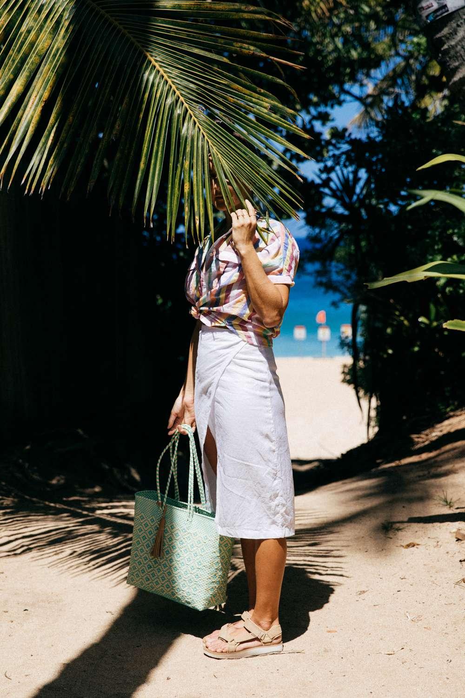 Tara Michie poses behind palm in Hawaii