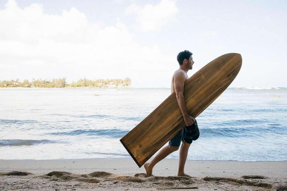 Tyler Rock holding traditional hawaiin surfboard on beach