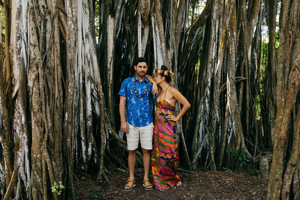Tara Michie and Tyler rock pose by tree in Hawaii