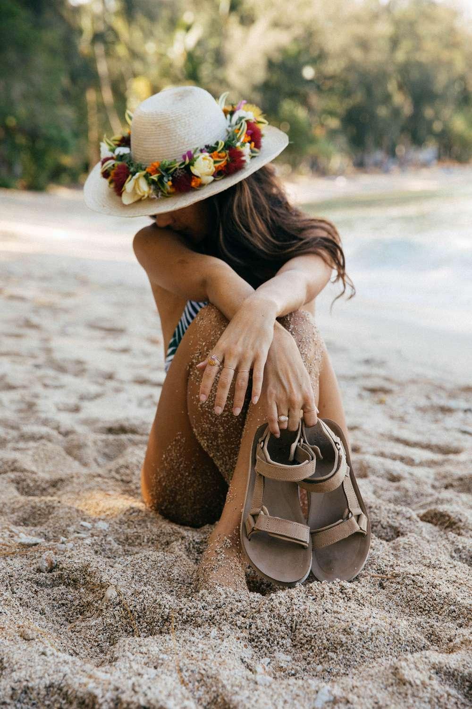 Tara Michie wearing hat and holding Teva sandals on beach