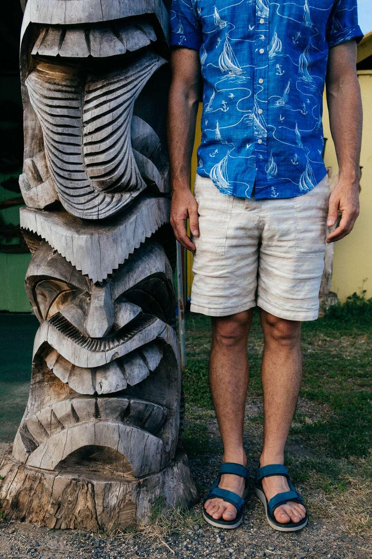 Tyler Rock wears Teva sandals by Hawaiian statue