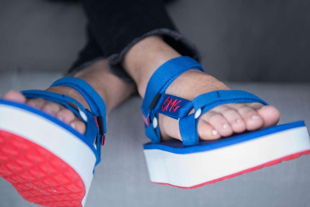 Feet wearing embroidered Teva flatform sandals.