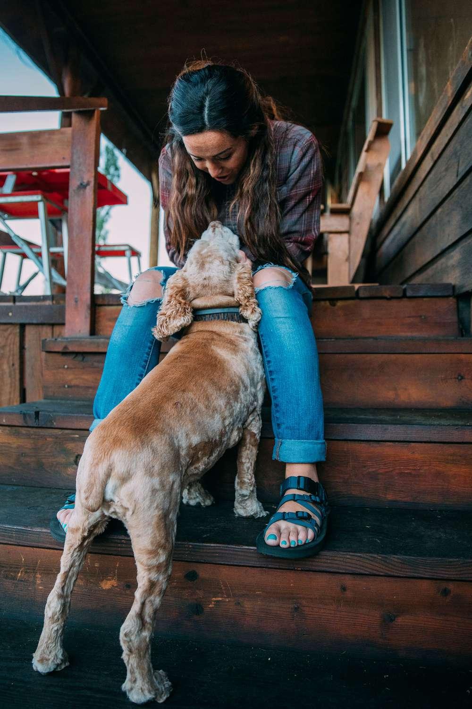 Girl on steps petting dog wearing Teva sandals.