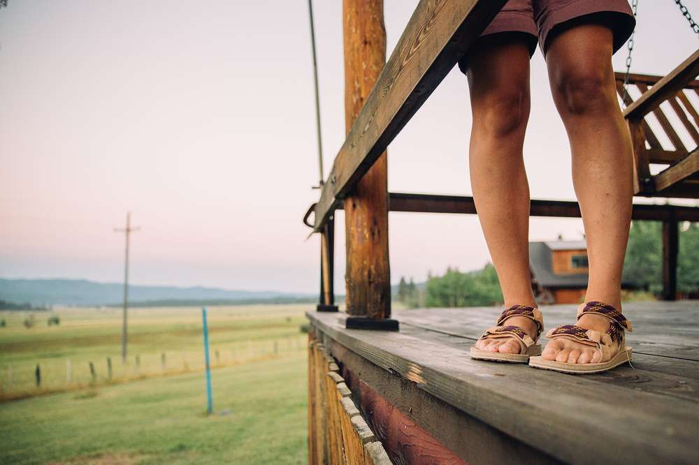Girl's feet wearing Teva on cabin porch
