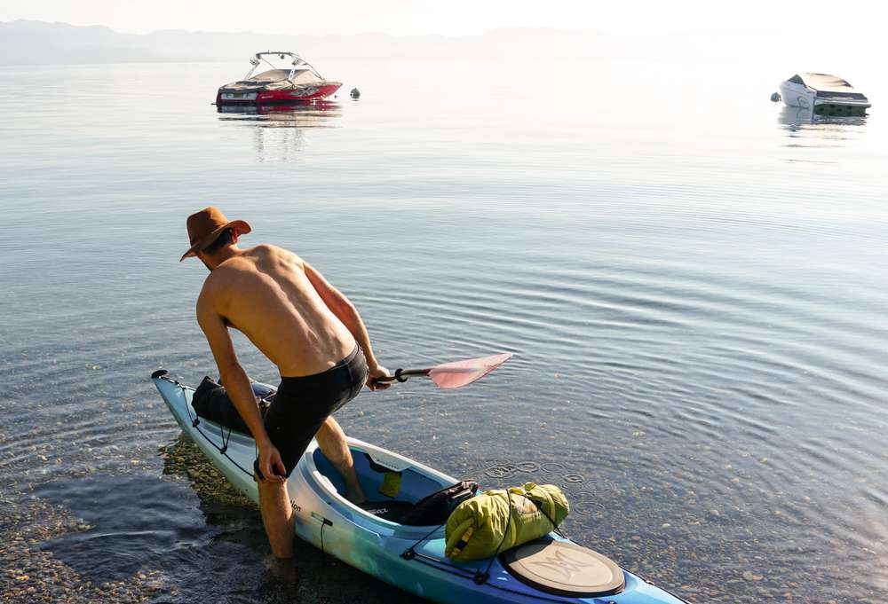 Photo of a man entering a kayak on Lake Tahoe
