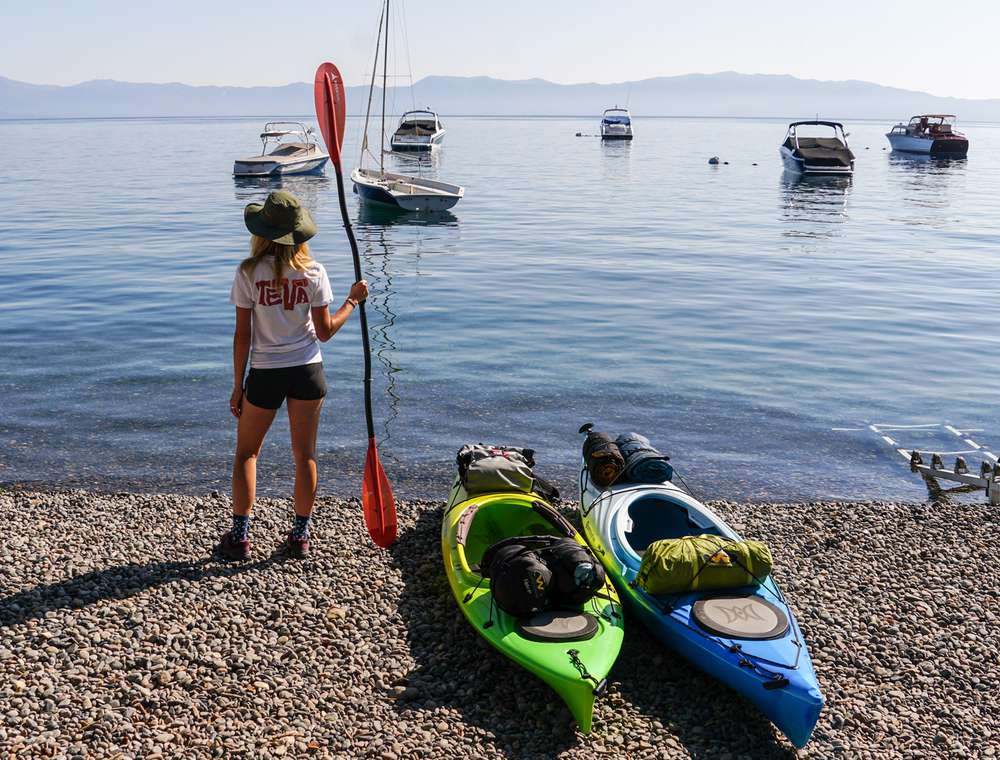 Photo of woman standing next to kayaks on Lake Tahoe.
