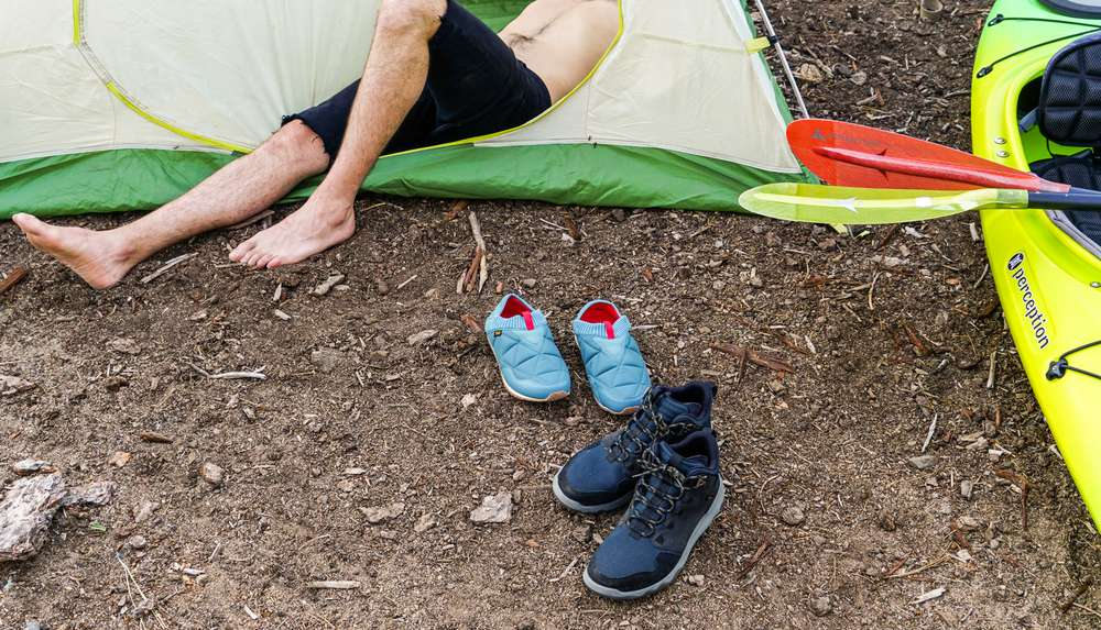 Photo of man sitting in tent next to shoes.