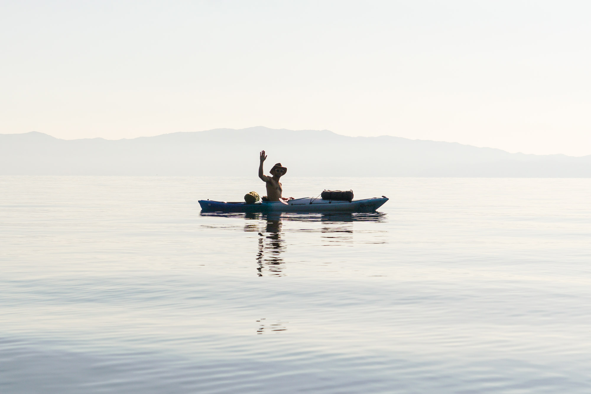 Photo of a man waving from a kayak.