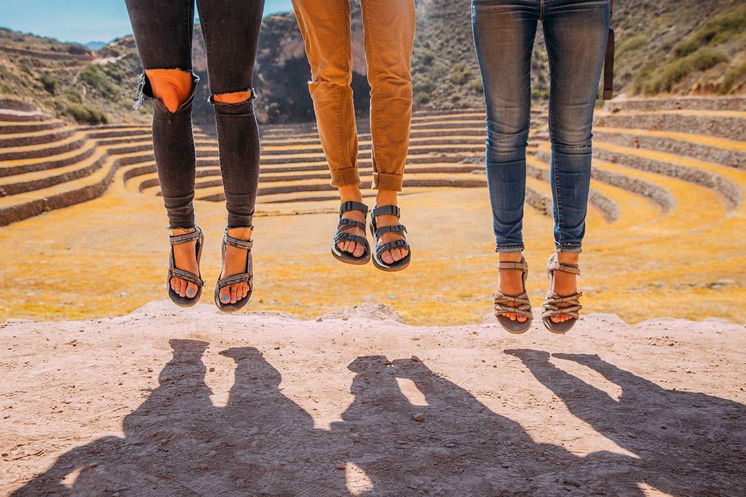 Three pairs of feet jumping wearing Teva sandals