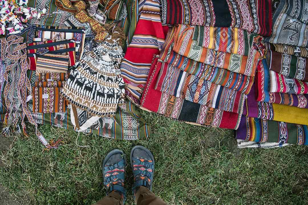 Feet next to a pile of textiles.