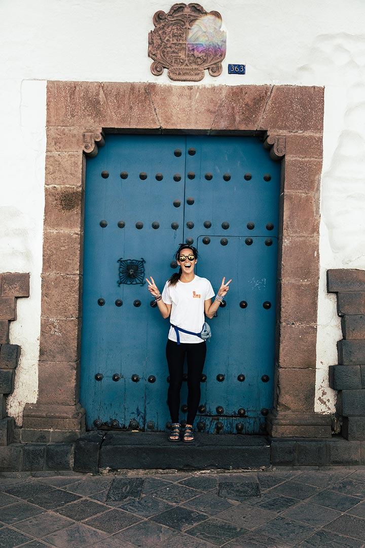 Woman standing in front of blue door.