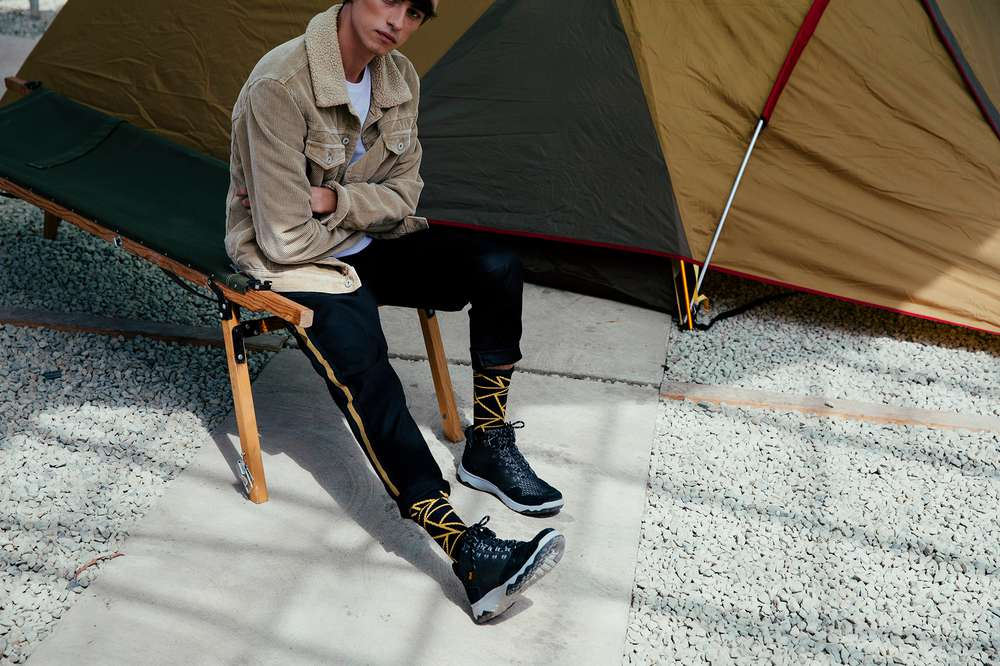 Man wearing the Teva Arrowood Flash boots by a tent.