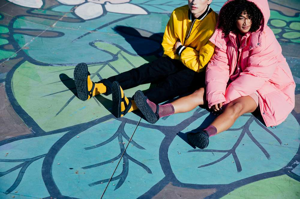 Man and women sitting wearing coats and Teva sandals.