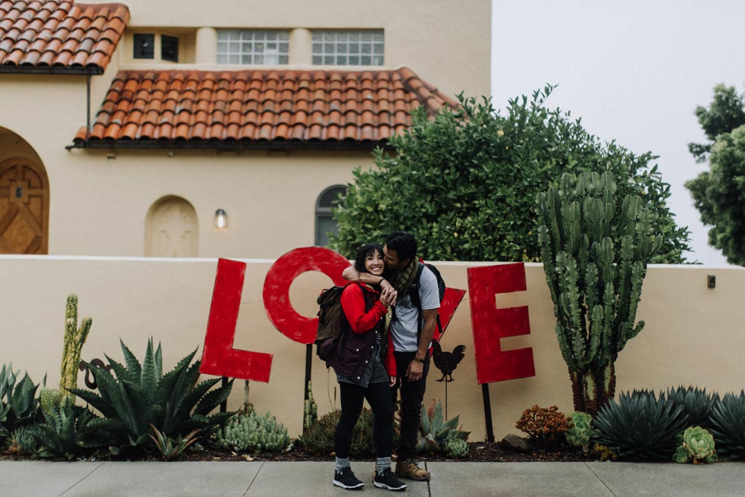 A couple kisses next to love sign in San Francisco