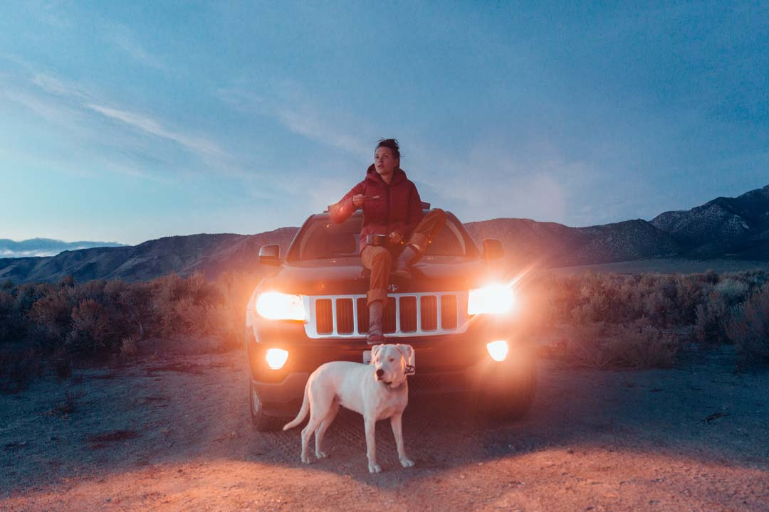 Woman and dog eat dinner next to car while camping.