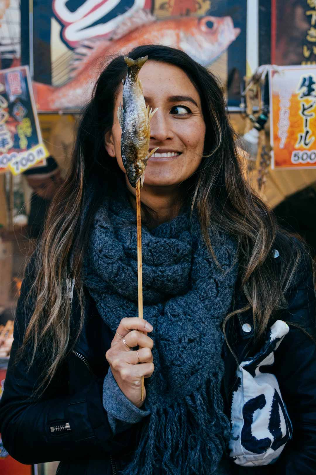 Woman holding fish on a stick in Japan.